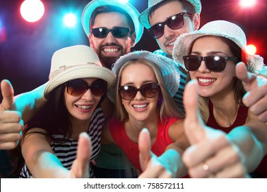 Happy young people showing OK sign in the night club