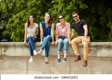 Happy young people sitting outdoors, smiling.