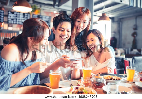 happy young people sitting in  restaurant and taking  photo for foods