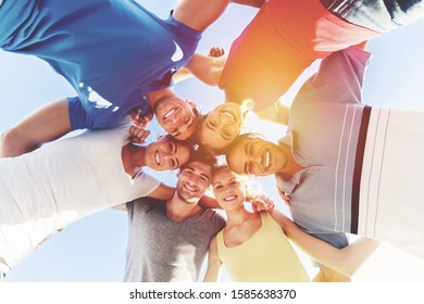 Happy young people standing in circle against blue sky
