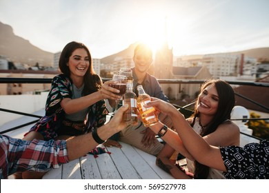 Happy young people toasting drinks at a rooftop party. Young friends hanging out and enjoying drinks.