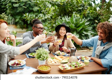 Happy young people toasting with glasses of homemade lemonade by festive dinner