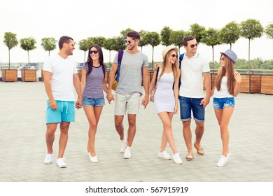 Happy young people walking on the road in summer day.