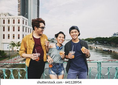 Happy young people with wide smiles holding sandwiches and plastic cups of iced tea in hands while leaning against bridge railing