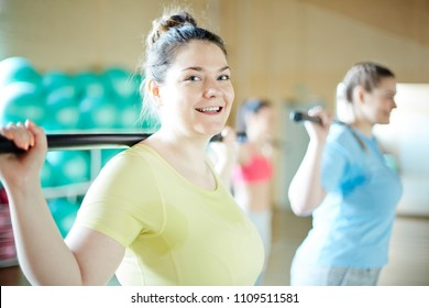 Happy young plus-sized woman and her friend exercising with gymnastic bars