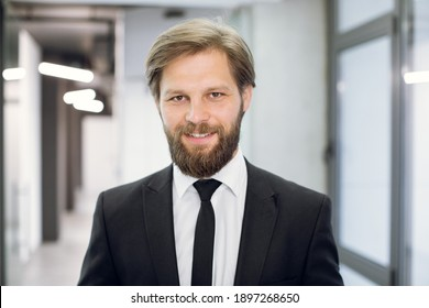 Happy young positive male office worker manager, wearing black suit and tie, smiling at camera, standing on the background of modern light office corridor. Close up face portrait