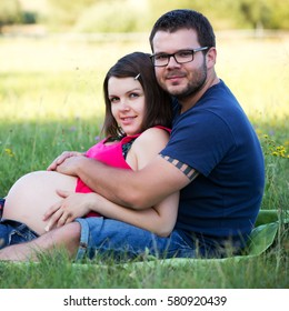 Happy and young pregnant couple is hugging in nature.