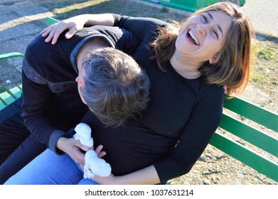 HAPPY YOUNG PREGNANT  COUPLE PLAYING IN THE STREET