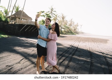 Happy young pregnant couple in stylish summer wear embracing and taking selfie on modern mobile phone while spending sunny weather on peaceful tropical seashore