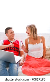 Happy young pregnant woman with husband shopping on Internet
