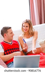 Happy young pregnant woman showing her husband what she likes to buy online