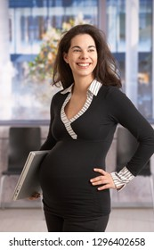 Happy young pregnant woman working in office, looking away, smiling.