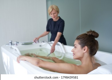 Happy young pretty woman during hydromassage in beauty salon sitting in hydrobath