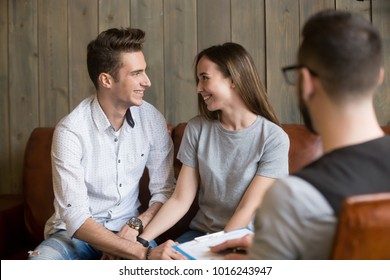 Happy young reconciled couple making up at therapy session with psychologist, relieved smiling husband and wife holding hands, effective family counseling or relationships conflict resolution concept