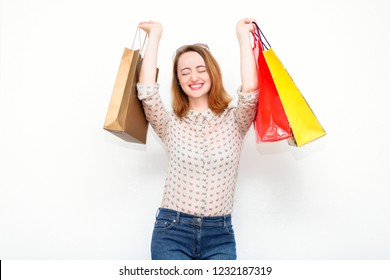 Happy young red-haired woman with bags after shopping smiling standing on a light background. Modern concept of fashion, style, shopping, sales and discounts.