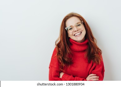 Happy young redhead woman with folded arms wearing glasses and a bright red sweater grinning happily at the camera over white with copy space