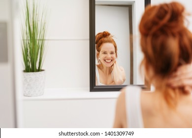 Happy young redhead woman grinning at her reflection in the bathroom mirror in an over the shoulder view