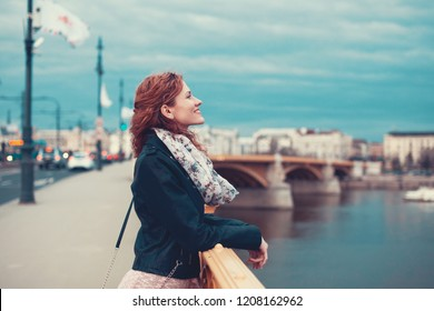 Happy young redhead woman in leather jacket smile on Margaret bridge, Budapest, Hungary