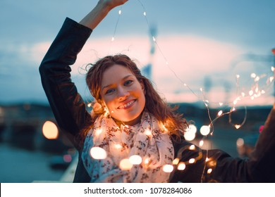 Happy young redhead woman playing with fairy lights outdoors and smile, teal and orange style