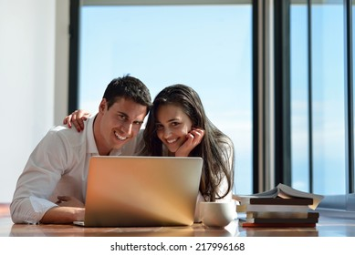 happy young relaxed  couple working on laptop computer at modern home indoor