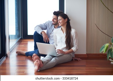 happy young relaxed  couple working on laptop computer at modern home interior