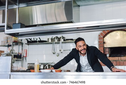 Happy young restaurant owner standing at kitchen counter looking away and smiling. Caucasian businessman in commercial kitchen.