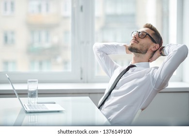 Happy young restful office worker in tie and white shirt sitting by desk against window and daydreaming at break