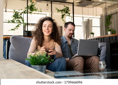 Happy young restful woman with cup of tea or coffee looking through window while sitting on couch next to her husband with laptop