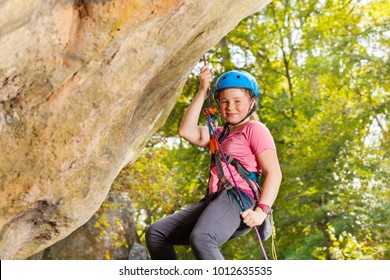 Happy young rock climber in helmet abseiling