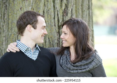 A happy, young and romantic couple looking into each others eyes on a sunny day.