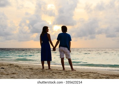 Happy young romantic couple on the beach at sunset