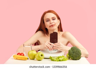 Happy young skinny woman exhausted by severe diets, holding chocolate bar, posing isolated on pink. Diet failure of emaciated redhead woman is eating unhealthy forbidden food with enormous pleasure.