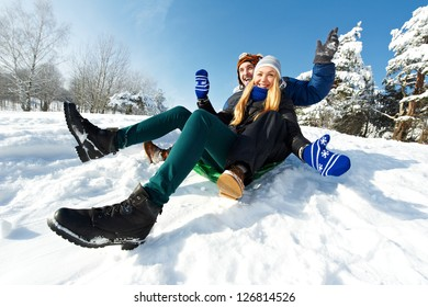 happy young smiling adult people in warm clothing sledding on snow at winter outdoors