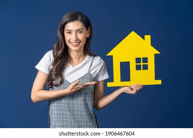 Happy young smiling Asian woman holding and Presenting yellow color house mockup paper on blue color background, thinking for investment, sales and insurance, building and property concept