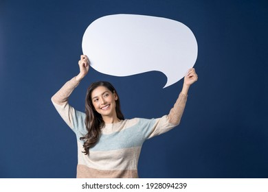 Happy young smiling Asian woman holding copy space empty message bubbles on blue color background, thinking and specking via balloon blank paper, Private opinion for advertisement Concept