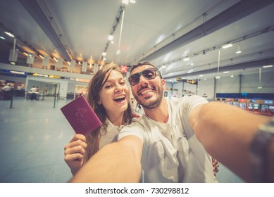 Happy young smiling caucasian couple traveler having fun at airport terminal holding passport. Travel and lover concept