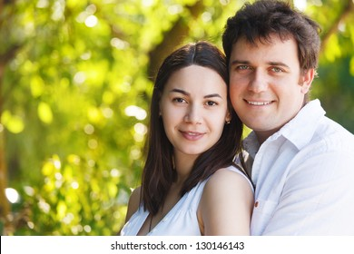 Happy young smiling couple in summer day outdoors