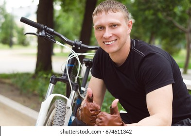 Happy young smiling man with bicycle showing thumbs up sign. Active life concept.