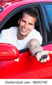 Happy young smiling man with a car key.