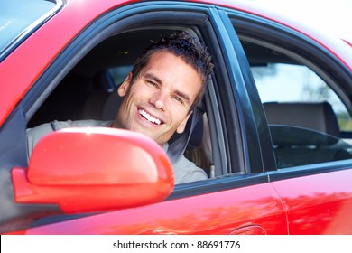 Happy young smiling man driving a new car.