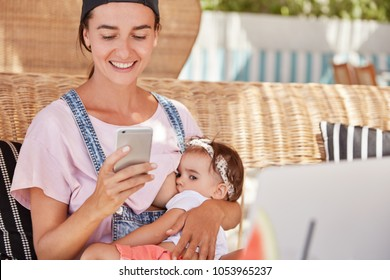 Happy young smiling mother in casual clothing breastfeeds her little baby, glad to recieve text message on smart phone, loves her child, does shopping online. Motherhood and maternity concept