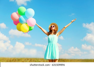 Happy young smiling woman with an air colorful balloons is enjoying a summer day over blue sky meadow background