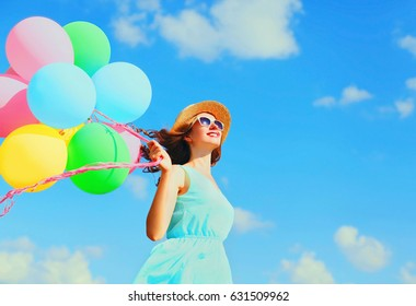 Happy young smiling woman with an air colorful balloons is having fun wearing a summer straw hat over blue sky background