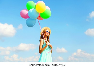Happy young smiling woman with an air colorful balloons is enjoying a summer sunny day over blue sky background
