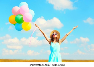 Happy young smiling woman with an air colorful balloons is enjoying a summer day on a meadow blue sky