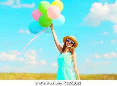 Happy young smiling woman with an air colorful balloons is enjoying a summer day over meadow blue sky background