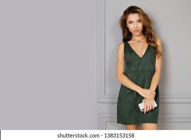 Happy young smiling woman holding smartphone. Portrait of her she nice looking sweet attractive lovely cheerful lady in green. Space for text