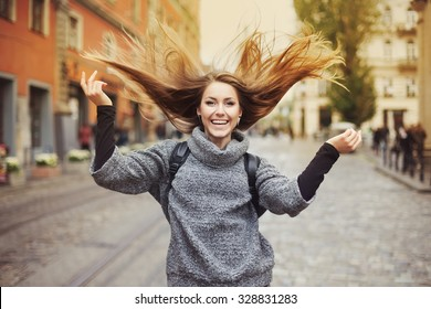 Happy young smiling woman playing with her long beautiful hair. Emotional portrait