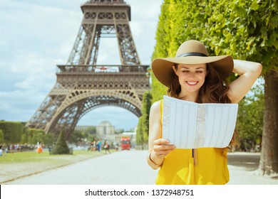 happy young solo tourist woman in yellow blouse and hat at Champ de Mars overlooking Eiffel tower in Paris, France looking at the map.