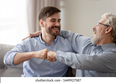 Happy young son and old father fists bumping, having fun together, celebrating success or greeting each other, mature aged dad and millennial man enjoying weekend, sitting on couch at home, close up